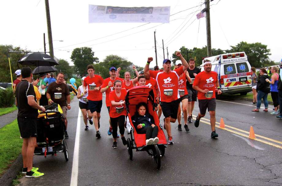 Members of myTEAM TRIUMPH, with Sami Leskin, of Westport, in a team wheelchair, approach the finish line after running in the Fairfield Police Department Sunset 5K at Penfield Beach in Fairfield, Conn., on Wednesday, July 25, 2018. myTEAM TRIUMPH is a new organization where volunteers pair with clients of the Norwalk nonprofit STAR to help people with disabilities be able to participate in races using specialized racing wheelchairs. Photo: Christian Abraham / Hearst Connecticut Media / Connecticut Post