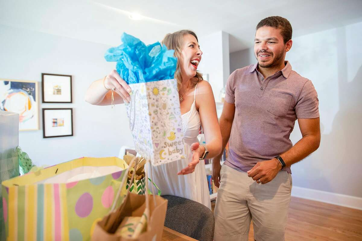 """Andrea Schwartz Boone and her husband Derrick Boone open presents during a their baby shower in Orinda, Calif. on Saturday, July 21, 2018. The couple used a new """"universal baby registry"""" called Baby List which allows expectant parents to not only register for items on the Baby List website but also gifts for charities, hands-on help with meals and chores, and meal deliveries."""