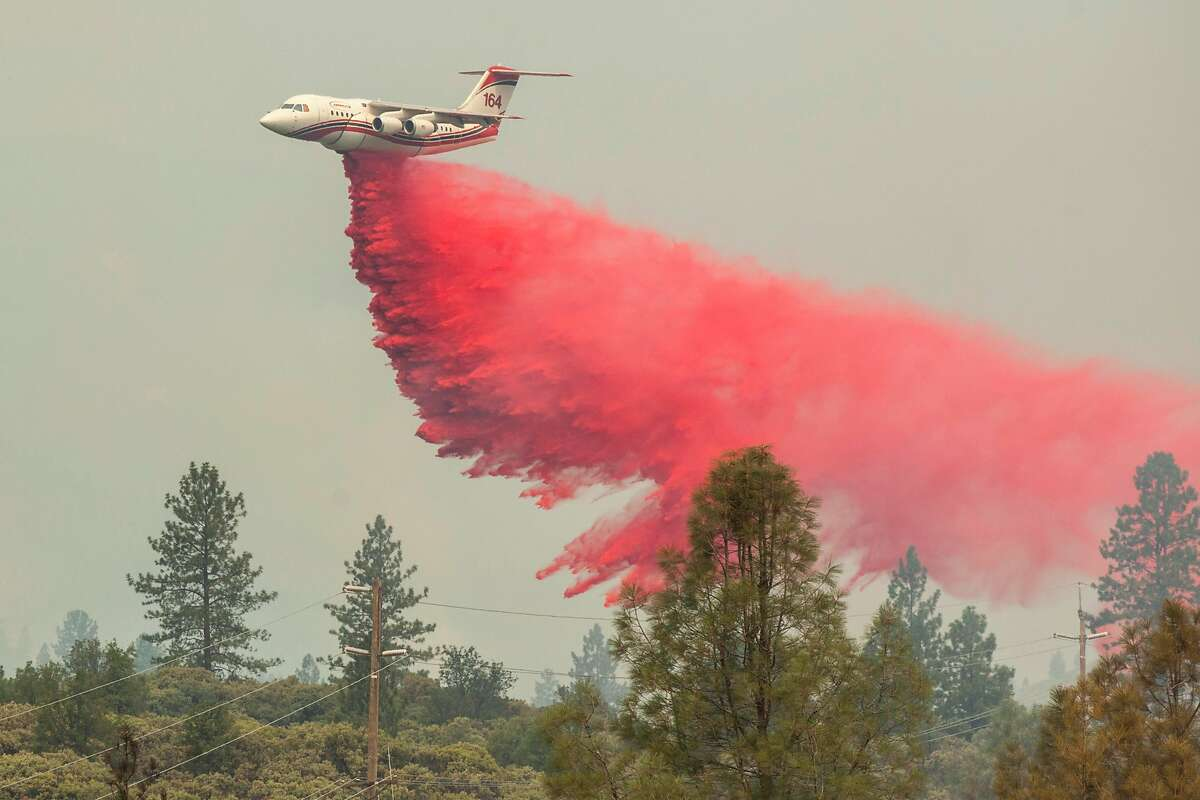 A fire retardant bomber drops it's payload on the Carr Fire as it burns out of control away from downtown Redding, Friday 27 July 2018 in Shasta, CA.