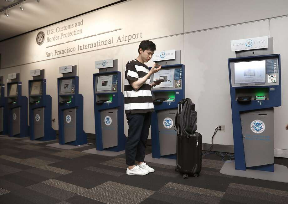 Kihyun Yoon checks in using the Global Entry computers at the U.S. Customs and Border Protection at the San Francisco International airport  Photo: Liz Hafalia / The Chronicle 2018