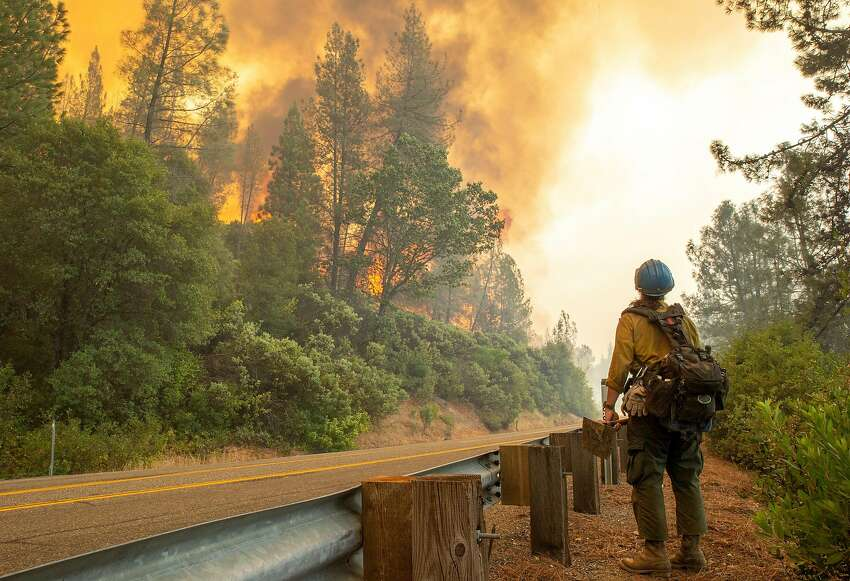 A member of the Tallac Hotshots crew watches the fire along Highway 299 for hotspots as the Carr Fire approaches on July 27, 2018, in Shasta County.