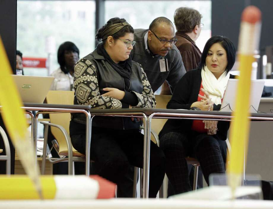 Affordable Care Act health insurance marketplace navigators Leticia Chaw, right, and Herb Shook, center, help get information for Jennifer Sanchez, left, to re-enroll in a health insurance plan Nov. 14, 2014, in Houston. ACA afforded states the opportunity to expand Medicaid. Texas didn't and leads the nation in the uninsured and is a national leader in people delaying health care because of cost. Photo: David J. Phillip /AP / AP