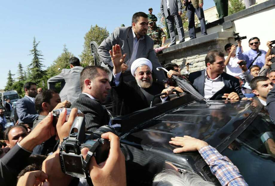 Iranian president Hassan Rouhani waves to supporters as his motorcade leaves Tehran's Mehrabad Airport upon his arrival from New York in 2013. President Trump recently threatened Iran after Rouhani issued its own warning. Photo: ATTA KENARE /AFP /Getty Images / AFP