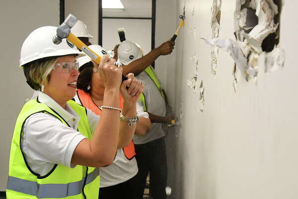 Jana Gonzales, left, is joined by all of her fellow Spring ISD Board of Trustees, as she knocks down a wall in the new Police Command Center on June 7, 2018. The remodeling of the 41,644-square-foot building will feature the new police headquarters and the district's tax, technology and risk management offices.
