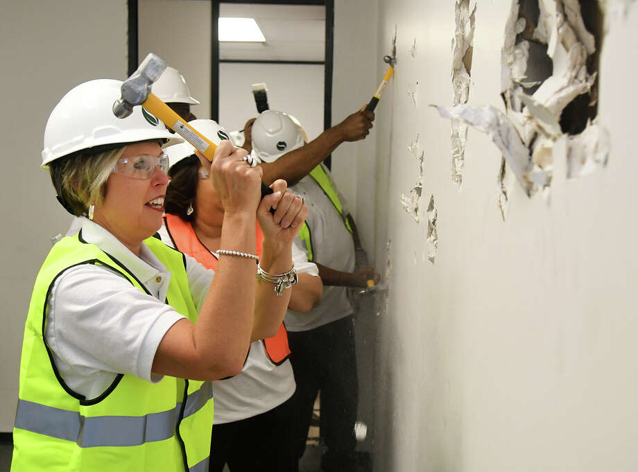 Jana Gonzales, left, is joined by all of her fellow Spring ISD Board of Trustees, as she knocks down a wall in the new Police Command Center on June 7, 2018. The remodeling of the 41,644-square-foot building will feature the new police headquarters and the district's tax, technology and risk management offices. Photo: Jerry Baker/For The Chronicle