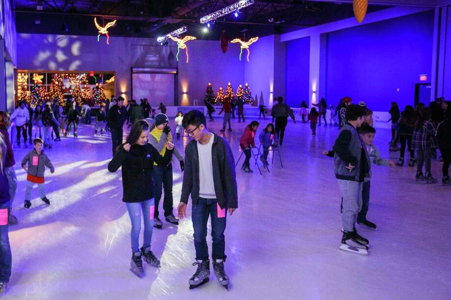 Ice rink patrons skate with one another at The Ice Rink at The Woodlands Town Center. The Ice Rink in The Woodlands Town Center opened on Nov. 16. and will have hours of availability through Jan. 20. The ice rink is located near the north gate entry of The Cynthia Woods Mitchell Pavilion at 2005 Lake Robbins Drive at the intersection of Six Pines Drive. Admissions for two-hour skate sessions are $12.50 for adults and 6$ for kids that are 5 years-old and younger. This includes skate rentals. Helmet and walker rentals are available for an additional cost. Hours of operation are Monday through Thursday from 3 to 9 p.m., Friday from 3 to 11 p.m., Saturday from 10 a.m. to 11 p.m., and Sunday from noon to 7 p.m. It will be open during holidays as well including Thanksgiving Day, Christmas Eve, Christmas Day, New Year's Eve, New Year's Day and school holidays based on the Conroe ISD calendar. Photo: Michael Minasi, Staff Photographer / Houston Chronicle / © 2017 Houston Chronicle