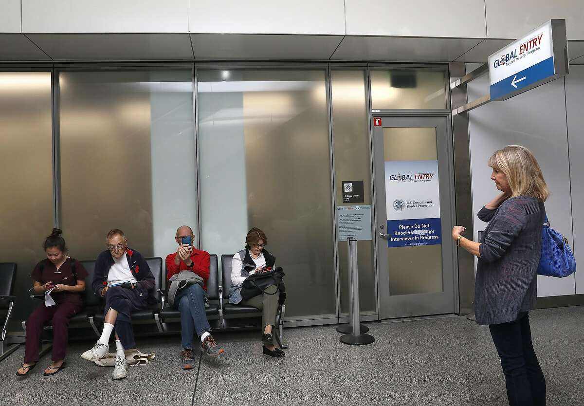 A line of people (left) wait for their Global Entry interview appointments at San Francisco International airport as Gayle Collins (right) tries to find out the status of her application on Thursday, July 26, 2018 in San Francisco, Calif.