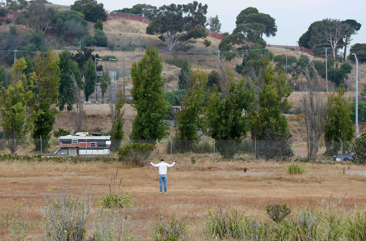 A man stretches in a vacant parcel of land at India Basin in San Francisco, Calif. on Wednesday, July 18, 2018. A developer is seeking approval to construct more than 1,500 homes on the site off of Innes Avenue and Arelious Walker Drive.