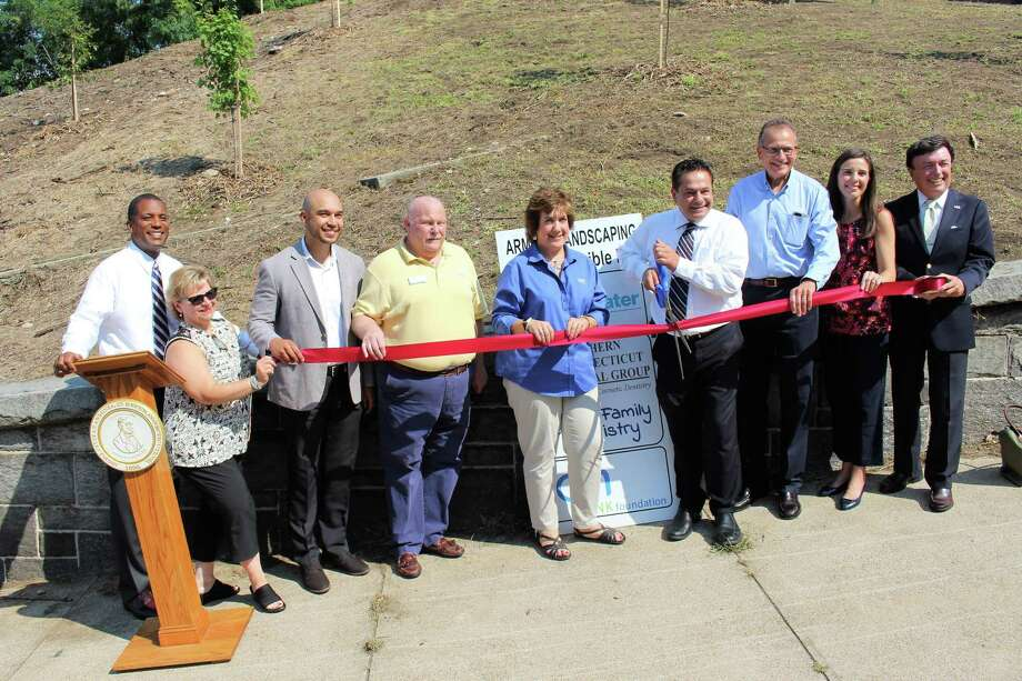 From left, state Sen. George Logan, state Rep. Linda Gentile, Dale Simonds of Southern Connecticut Dental Group, Robert Rose of Ion Bank, Kathleen McPadden of Ion Bank, Mayor David Cassetti, Chuck Boulier of Ion Bank, Beth Nesteriak of the Regional Water Authority and Tom Clifford of the Regional Water Authority celebrate beautification of the Ansonia Armory Friday. Photo: Jean Falbo-Sosnovich / For Hearst Connecticut Media