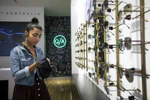 Sales associate Lilibeth Cardenas cleans sunglasses the new location inside the Galleria on Friday, July 27, 2018 in Houston. Cardenas was a fan of the sunglasses since 2015 and was excited for the opportunity to work at one of their new stores. Shopping centers like the Galleria have seen more e-commerce companies opening physical brick-and-mortar locations.