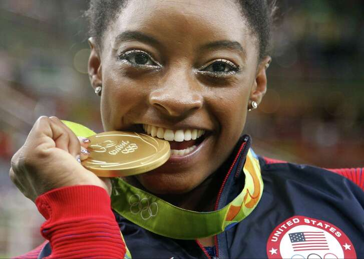 Simone Biles bites her gold medal for the all-around final at the 2016 Summer Olympics.
