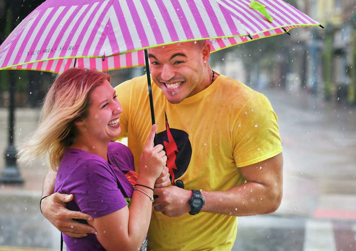 Nakya Fitzpatrick and Elliot Bennermon of Cohoes huddle under an umbrella as a thunder storm rolls through Friday July 27, 2018 in Schenectady, NY. (John Carl D'Annibale/Times Union)