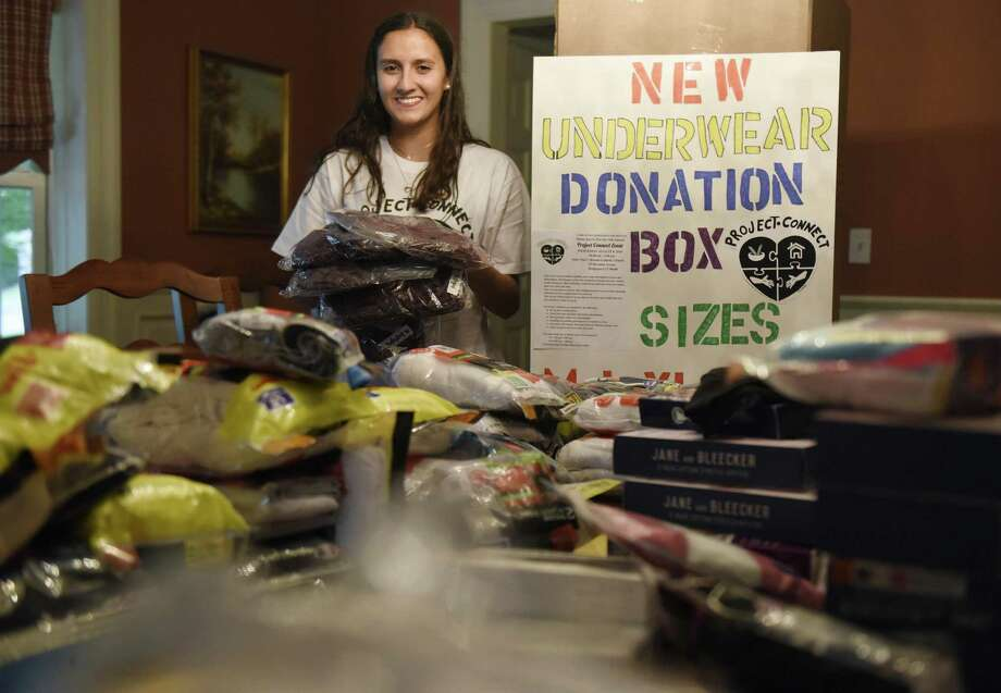 GHS rising senior Allison Brea poses with a collection sign and more than 1,000 pairs of new donated underwear and bras at her home in Old Greenwich. Photo: Tyler Sizemore / Hearst Connecticut Media / Greenwich Time