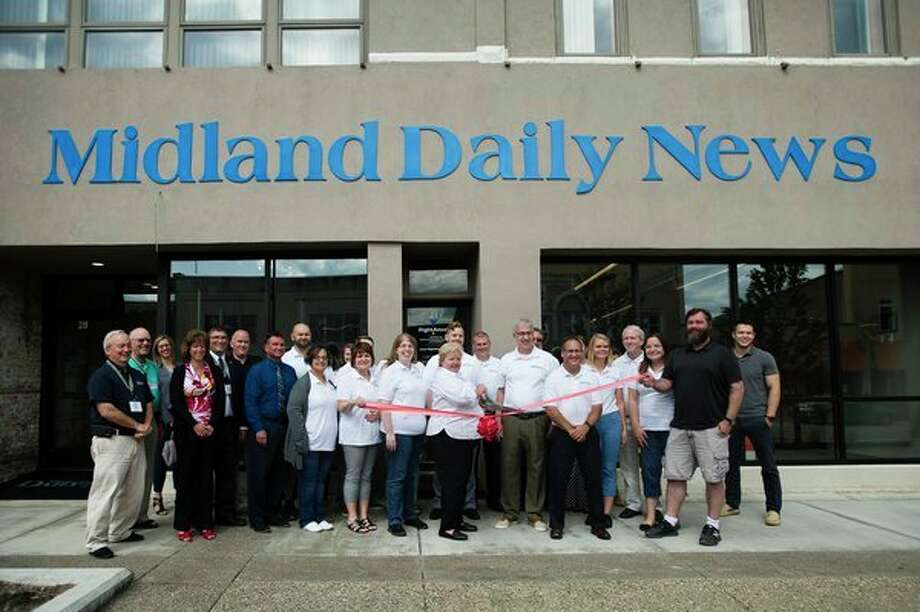 Staff of the Midland Daily News, along with Chamber of Commerce ambassadors, pose for a photo during a ribbon cutting ceremony at the new downtown office of the Midland Daily News on Thursday, July 26, 2018. (Katy Kildee/kkildee@mdn.net)