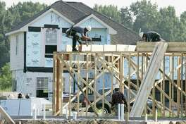 Construction workers build a new home Tuesday, Aug. 22, 2006 in Houston. Sales of new homes dropped in July by the largest amount since February while the inventory of unsold homes climbed to a record high. (AP Photo/David J. Phillip)