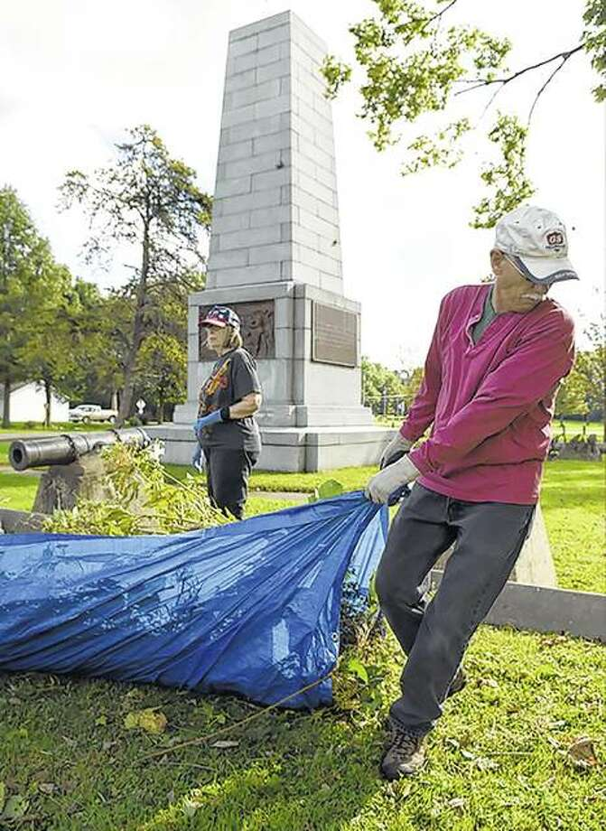 Volunteers Karin Ciaccio and David Keenan Miles work to clear brush from the river view of the Campbell's Island monument. The monument commemorates a battle between U.S. soldiers and American Indians during the War of 1812. Photo:       Todd Mizener | Dispatch-Argus