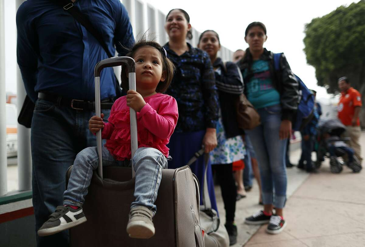 Merari Calderon, of El Salvador, lines up with her father, Alexander Calderon, left, to cross into the U.S. to begin the process of applying for asylum Thursday, July 26, 2018, near the San Ysidro port of entry in Tijuana, Mexico. As the Trump administration faced a court-imposed deadline Thursday to reunite thousands of children and parents who were forcibly separated at the U.S.-Mexico border, asylum seekers continue to arrive to cities like Tijuana, hoping to plead their cases with U.S. authorities. (AP Photo/Gregory Bull)