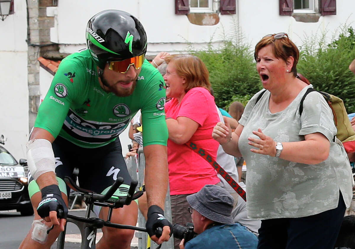 A spectator cheers Slovakia's Peter Sagan as he rides during the twentieth stage of the Tour de France cycling race, an individual time trial over 31 kilometers (19.3 miles) with start in Saint-Pee-sur-Nivelle and finish in Espelette, France, Saturday, July 28, 2018.