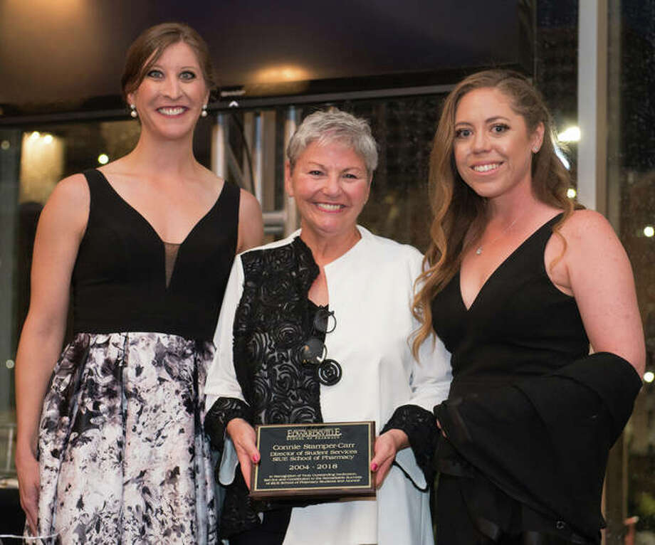 """SIUE School of Pharmacy alumnae Maggie Krumwiede (left) and Kelly Kleeman (right) presented a plaque """"in recognition of truly outstanding dedication"""" to retiring director of Student Services Connie Stamper-Carr. Photo:       For The Telegraph"""