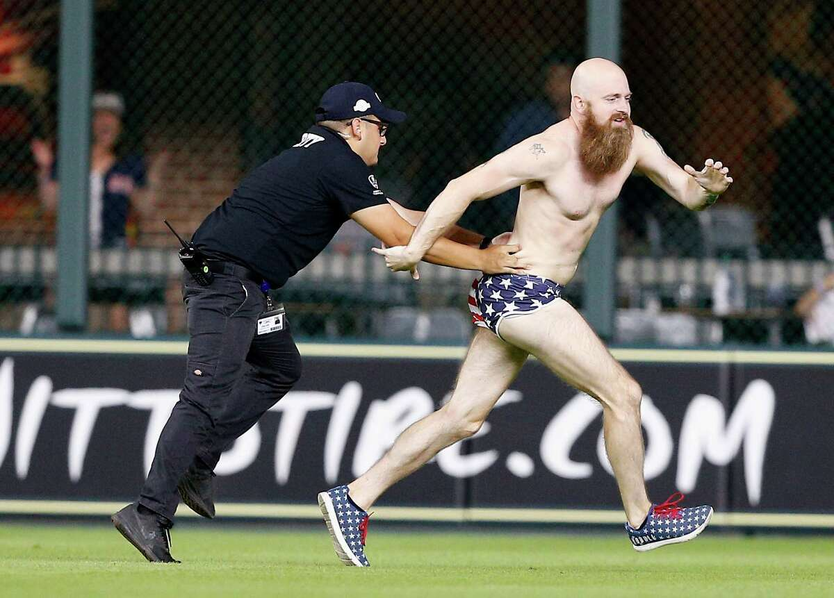 HOUSTON, TX - JULY 27: Security attempts to apprehend a fan that ran into the field at the end of the game between the Texas Rangers and the Houston Astros at Minute Maid Park on July 27, 2018 in Houston, Texas.