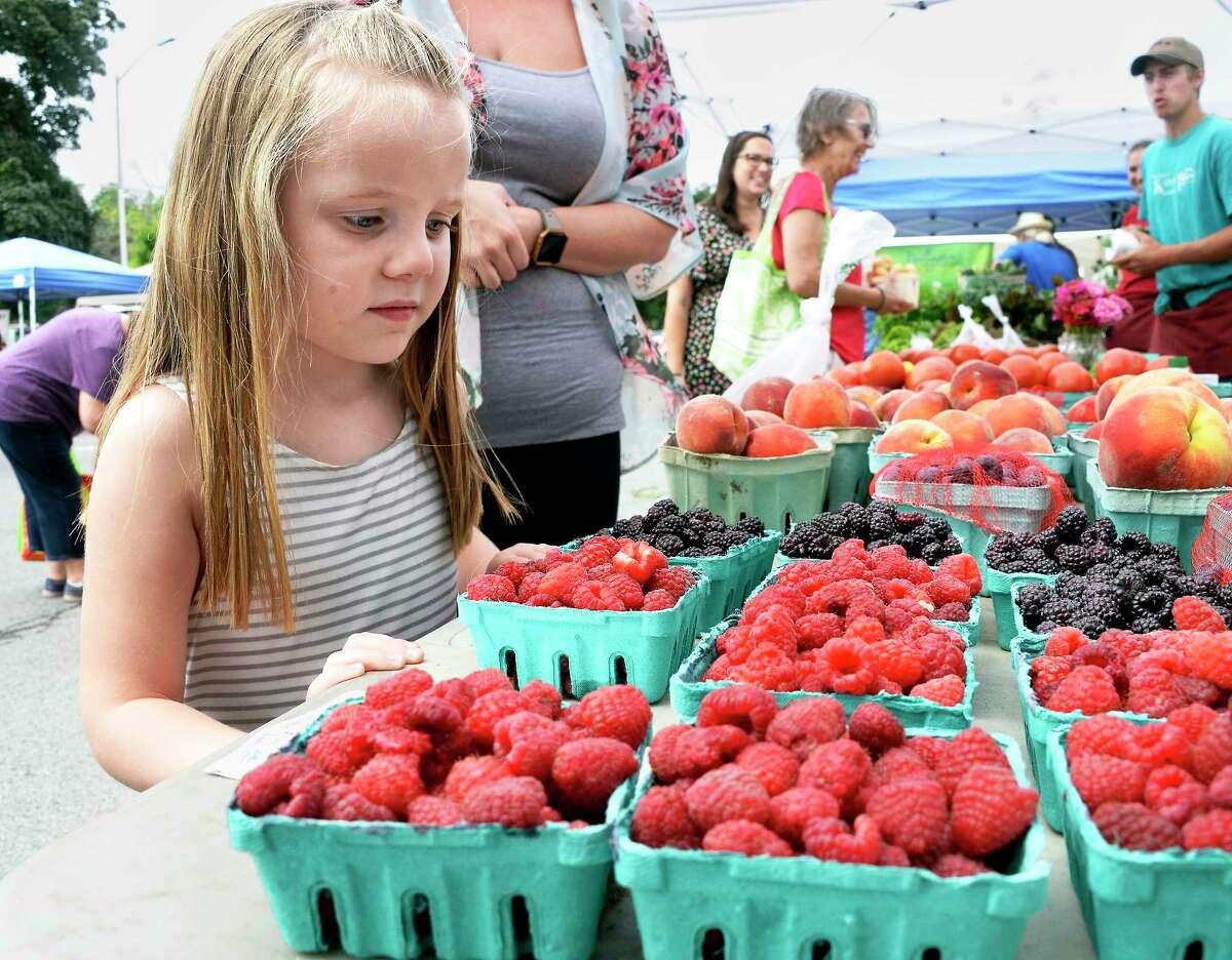 Four-year-old Vivienne Korzatkowski of Delmar eyes freshly picked raspberries from Kristy's Barn in Schodack at the Delmar Farmers' Market at the Bethlehem Central Middle School Saturday July 28, 2018 in Delmar, NY.