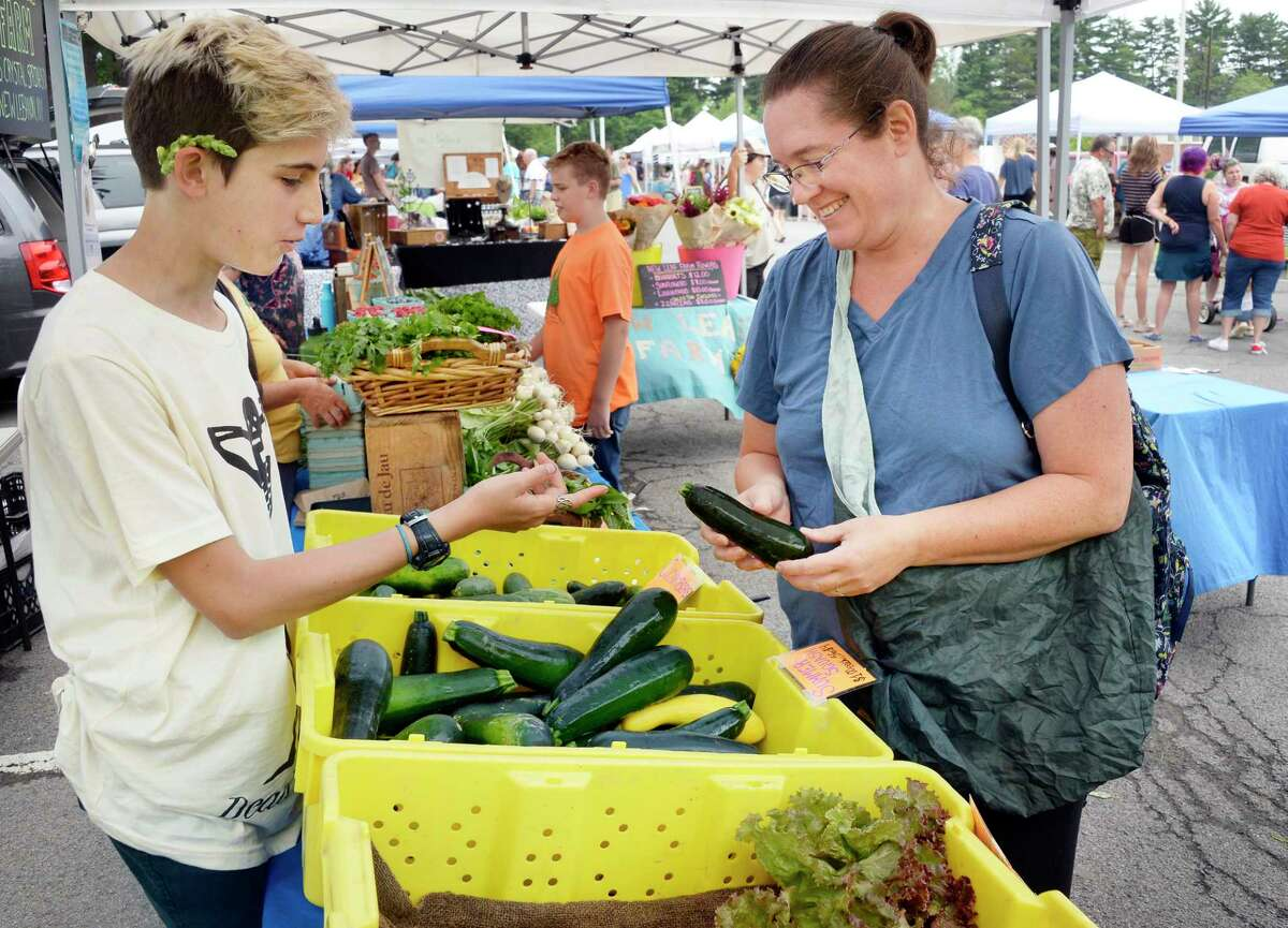 Phoenix Libsch, 14, left, of New Leaf Farm in New Lebanon helps Lauralee Holtz of Delmar pick out some summer squash at the Delmar Farmers' Market at the Bethlehem Central Middle School Saturday July 28, 2018 in Delmar, NY.
