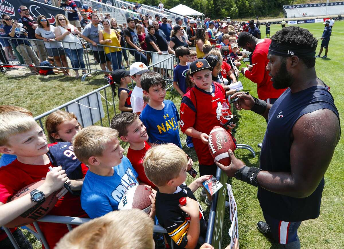 Houston Texans defensive tackle Brandon Dunn signs autographs after practice during training camp at the Greenbrier Sports Performance Center on Saturday, July 28, 2018, in White Sulphur Springs, W.Va.