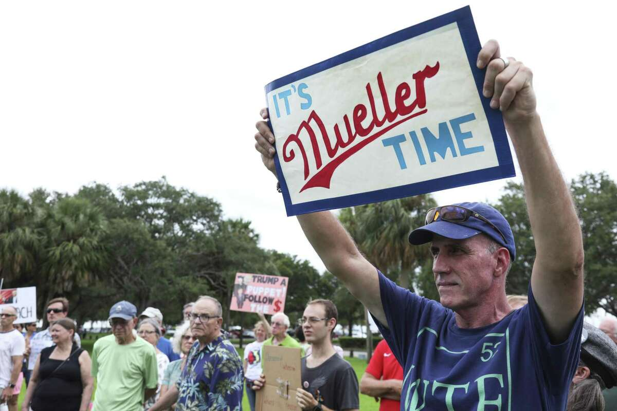 """Daniel Quinn of St. Petersburg holds a sign with the phrase """"It's Mueller Time"""" during a rally at Demens Landing in St. Petersburg, Fla., on Wednesday, July 18, 2018. Protesters were rallying against President Trump's denial earlier this week of Russian collusion in the 2016 election. (Eve Edelheit/Tampa Bay Times via AP)"""
