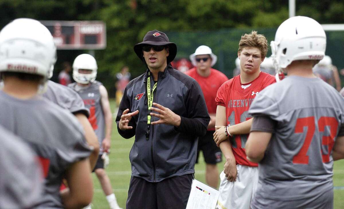 Greenwich coach John Marinelli reviews plays with his team during the first day of fall practice last season. The NSCA recently selected the Greenwich football team as a 2018 Strength of America Award recipient. The award recognizes the Cardinals' football program to have represented the gold standard in strength and conditioning.