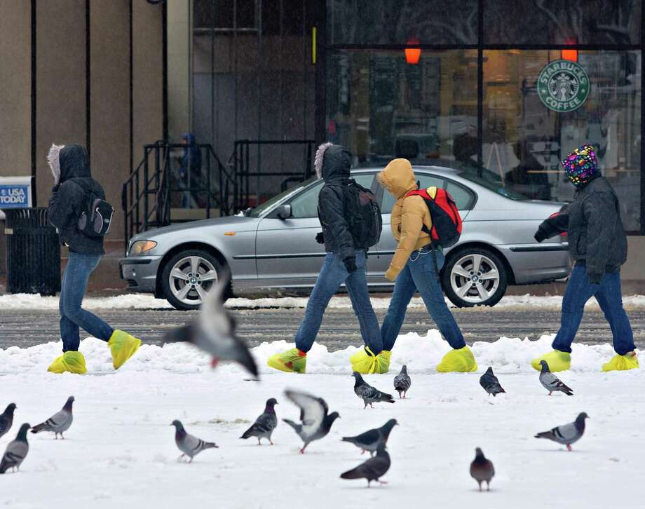 Improvising with plastic bags to get across downtown New Haven with dry feet as snow fell. Photo: Hearst Connecticut Media File Photo