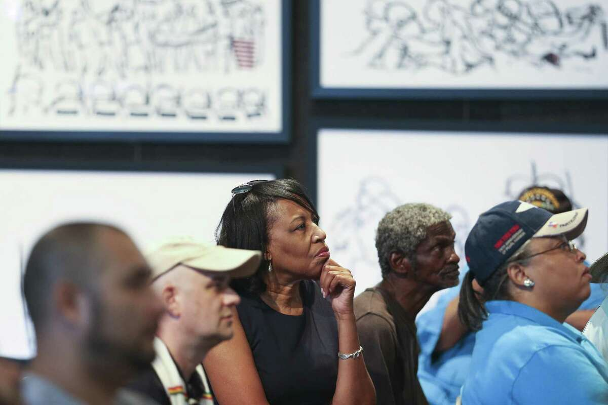 Debra Lacy, center, listens to a lecture by artist Ted Ellis at the Military Inspired Art exhibit at the Buffalo Soldiers National Museum during Buffalo Soldiers Day Saturday July 28, 2018 in Houston. The day commemorates the formation of the first all African American Army regiments in 1866.