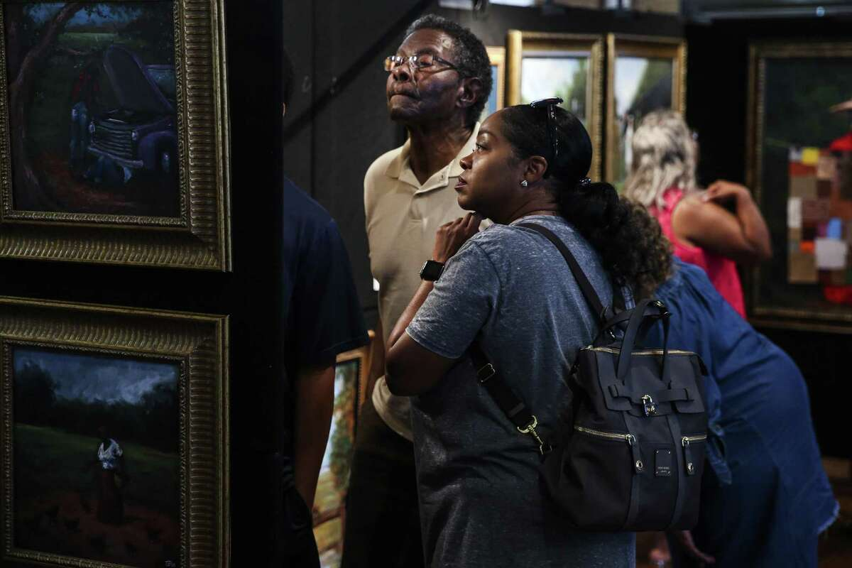 George Powell, left, and his daughter, Melanie Powell Rey, right, look at works in the Military Inspired Art exhibit at the Buffalo Soldiers National Museum during Buffalo Soldiers Day Saturday July 28, 2018 in Houston. The day commemorates the formation of the first all African American Army regiments in 1866.
