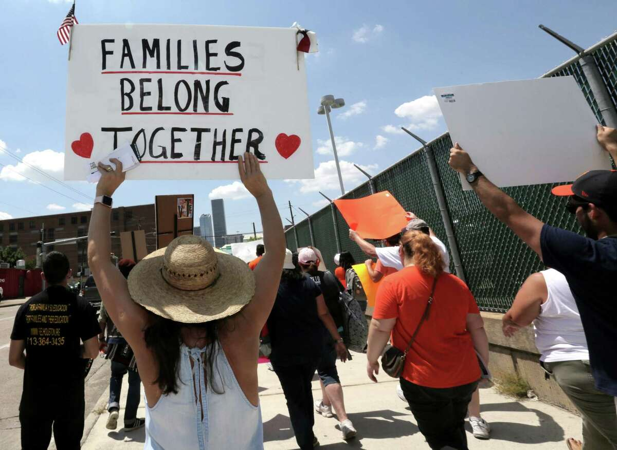 Marchers hold signs as they make their way to the site of the proposed detention center at 419 Emancipation Avenue to call for the reunification of immigrant families separated by the Trump Administration on Saturday, July 28, 2018 in Houston.