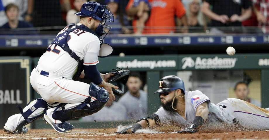 The throw is late to Houston Astros catcher Max Stassi, left, as Texas Rangers' Rougned Odor scores on his inside-the-park home run during the fifth inning of a baseball game Saturday, July 28, 2018, in Houston. (AP Photo/Michael Wyke) Photo: Michael Wyke/Associated Press