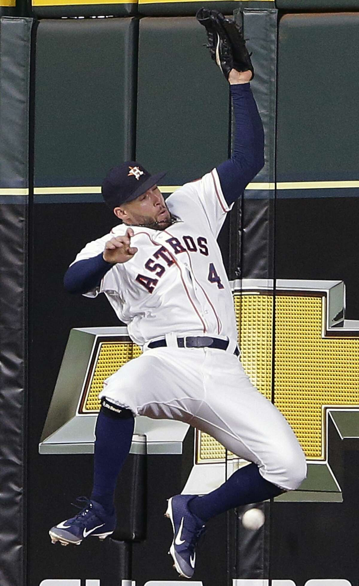 Houston Astros center fielder George Springer (4) misses a catch against the center field wall on the inside-the-park home run by Texas Rangers' Rougned Odor (12) during the fifth inning of a baseball game Saturday, July 28, 2018, in Houston. (AP Photo/Michael Wyke)