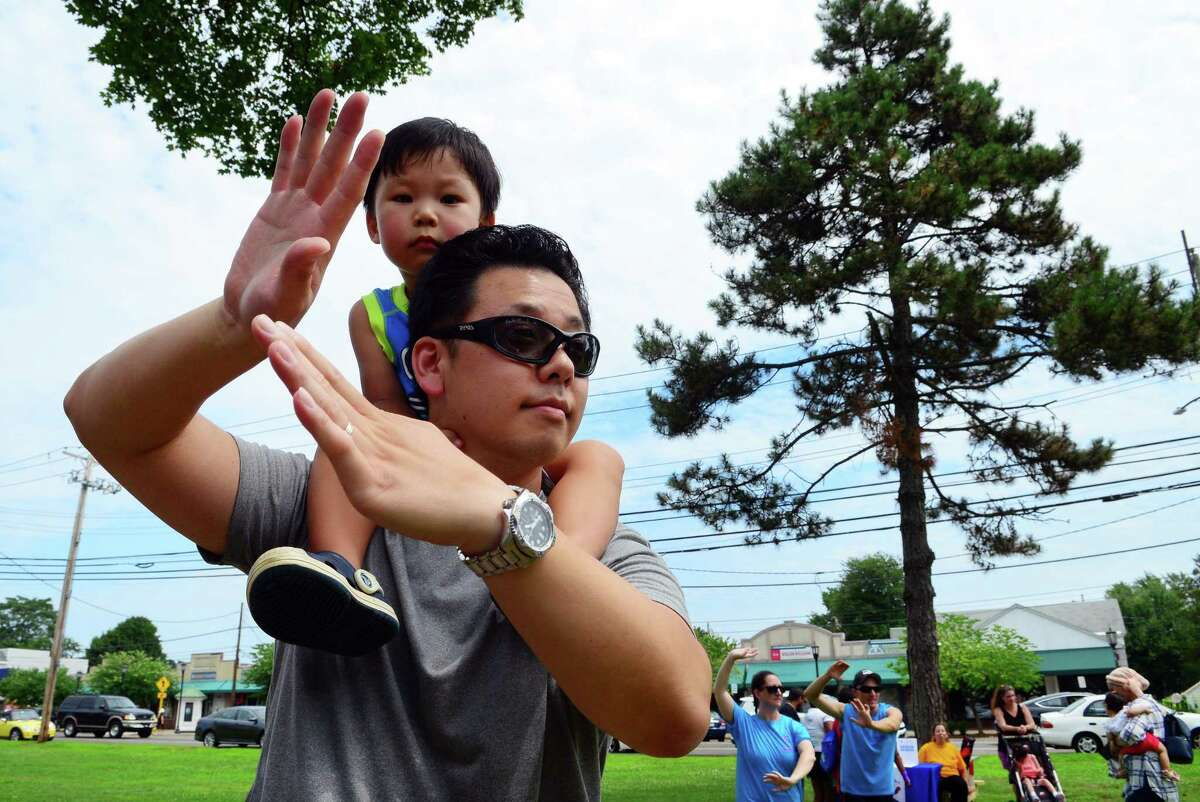 Daniel Chung, 3, sits on his dad Patrick's shoulder as he does Tai chi during the Family Fitness Day on Paradise Green in Stratford, Conn., on Saturday, July 28, 2018. The event, held by Get Healthy CT, coincides with National Dance Day and encourages area residents of all ages to be physically active and eat healthy foods.