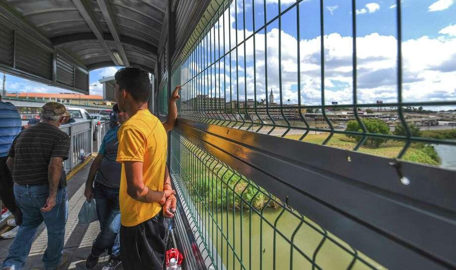 Estados Unidos es visto a la distancia mientras que inmigrantes cubanos y mexicanos, algunos preparándose para solicitar asilo, esperan en el lado mexicano del Puente Internacional Puerta de las Américas el sábado 16 de junio de 2018. Photo: Danny Zaragoza /Laredo Morning Times