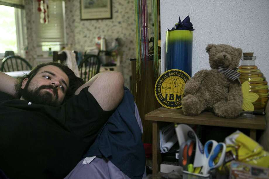 Benjamin Munoz looks over at the stuffed teddy bear that he gave his now fiance Abril Cardenas for their anniversary and survived the fire that destroyed their Iconic Village apartment building as he reclines in a chair at his family's home in San Antonio July 26, 2018. Photo: Josie Norris, Staff / San Antonio Express-News / © San Antonio Express-News
