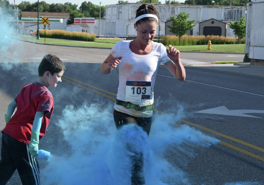 Megan Scott of Jacksonville gets covered with blue powder by Eli Strambaugh, 5, at the final checkpoint of Prairieland United Way's Colors United 5K run/walk Saturday.