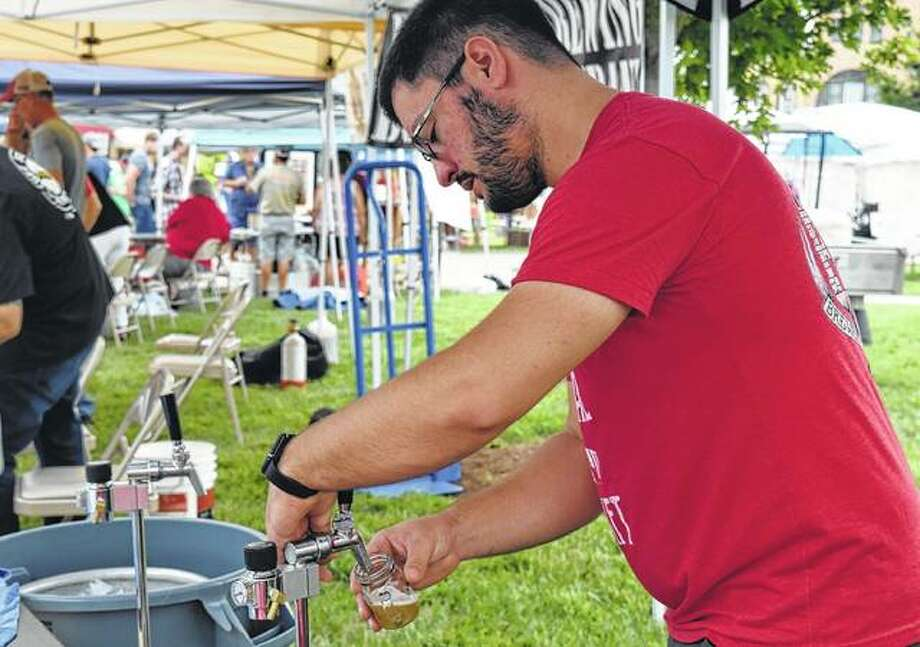 John Zerkle from Anvil and Forge Brewing and Distilling of Springfield draws a beer sample during the 2018 Craft Brew Festival and Midwest Makers and Artisan Market on Saturday. Photo:       Samantha McDaniel-Ogletree | Journal-Courier
