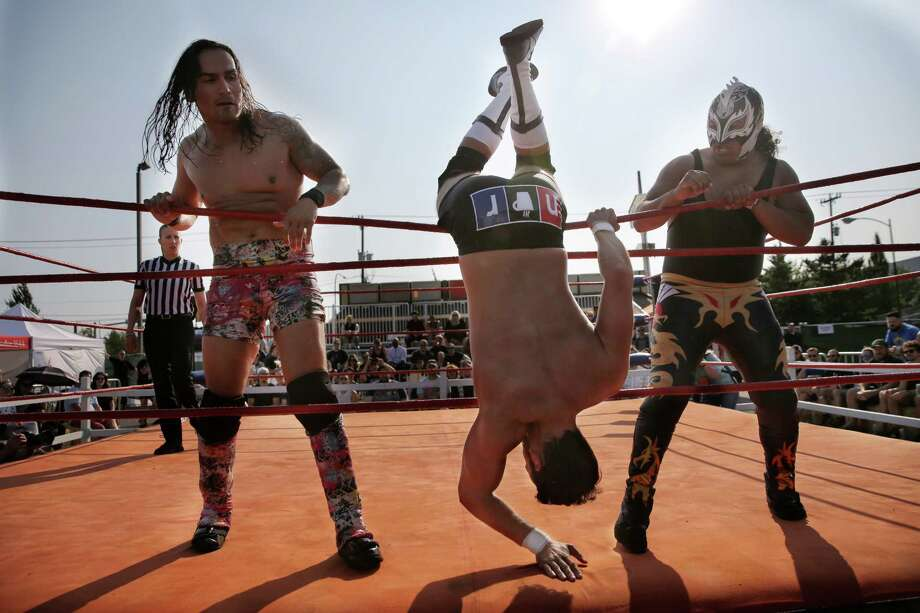 """Mannie Rioz, left, and Dorado, right, send Nick Radford, aka """"Vegan Delight"""", flying during the 2nd annual Backyard Bunkhouse BBQ Brawl and Rockin Wrestling Rager, which featured pro wrestling matches, gratuitous amounts of PBR and bands rocking the Randy's Restaurant parking lot in Tukwila, July 28, 2018. Photo: GENNA MARTIN, GENNA MARTIN, SEATTLEPI / Genna Martin"""