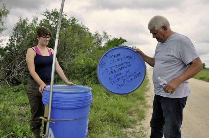 Eddy Canales, right, with a volunteer leave gallons of water inside plastic barrels for people crossing border. The barrels are at stations across South Texas to help avoid immigrant deaths from dehydration.