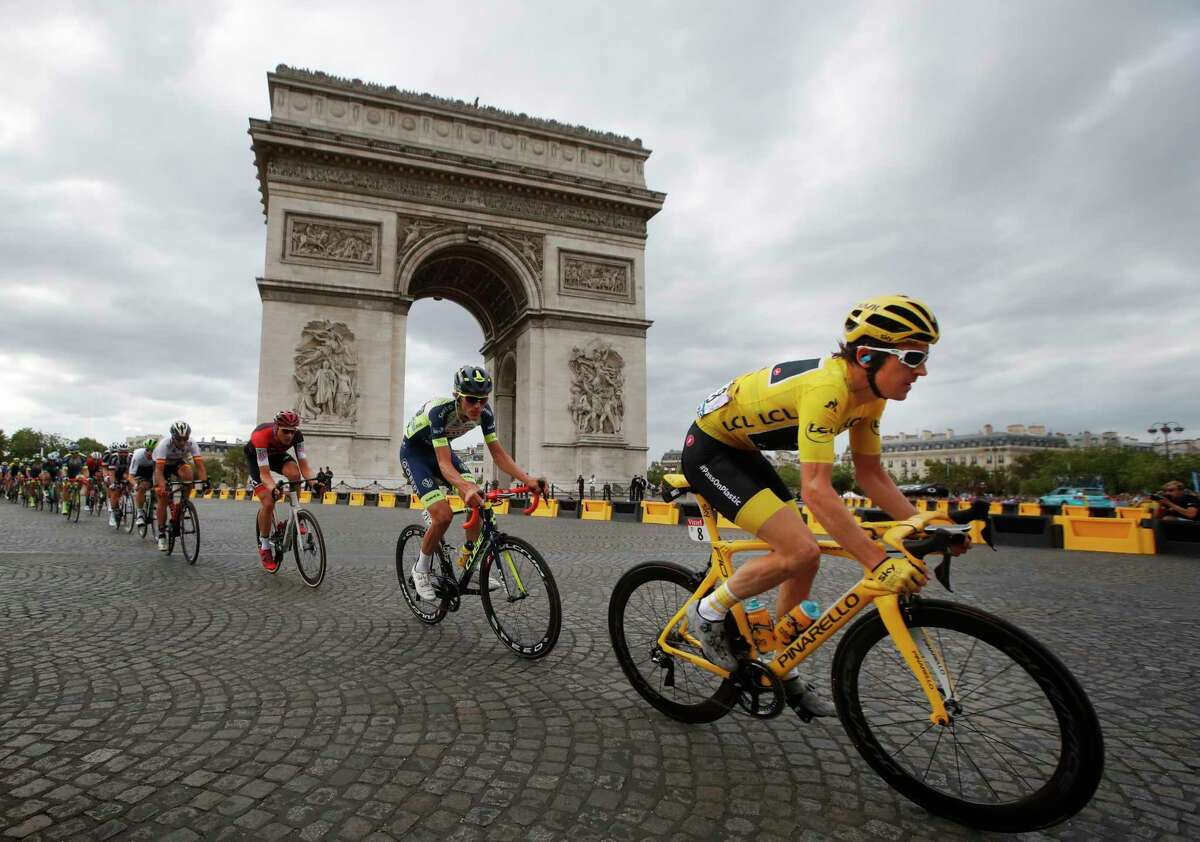 Tour de France winner Britain's Geraint Thomas, wearing the overall leader's yellow jersey, passes the Arc de Triomphe during the twenty-first stage of the Tour de France cycling race over 116 kilometers (72.1 miles) with start in Houilles and finish on Champs-Elysees avenue in Paris, France, Sunday July 29, 2018.