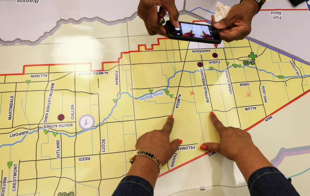 Almeda Plaza residents Bernadine Wilturner, top, and Mary Booker take photographs of their concerned flooding areas during Hurricane Harvey on a map during June 5, 2018, community meeting on the proposed $2.5 billion flood bond approved by voters four months five months later. ( Yi-Chin Lee / Houston Chronicle )