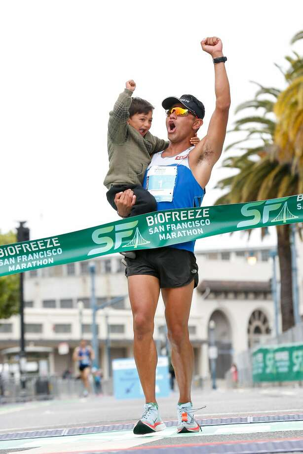 Winner of the men's Biofreeze San Francisco Marathon, Jorge Maravilla, crosses the finish line with son, Joaquin, on Sunday, July 29, 2018 in San Francisco, California. Photo: Amy Osborne, Special To The Chronicle