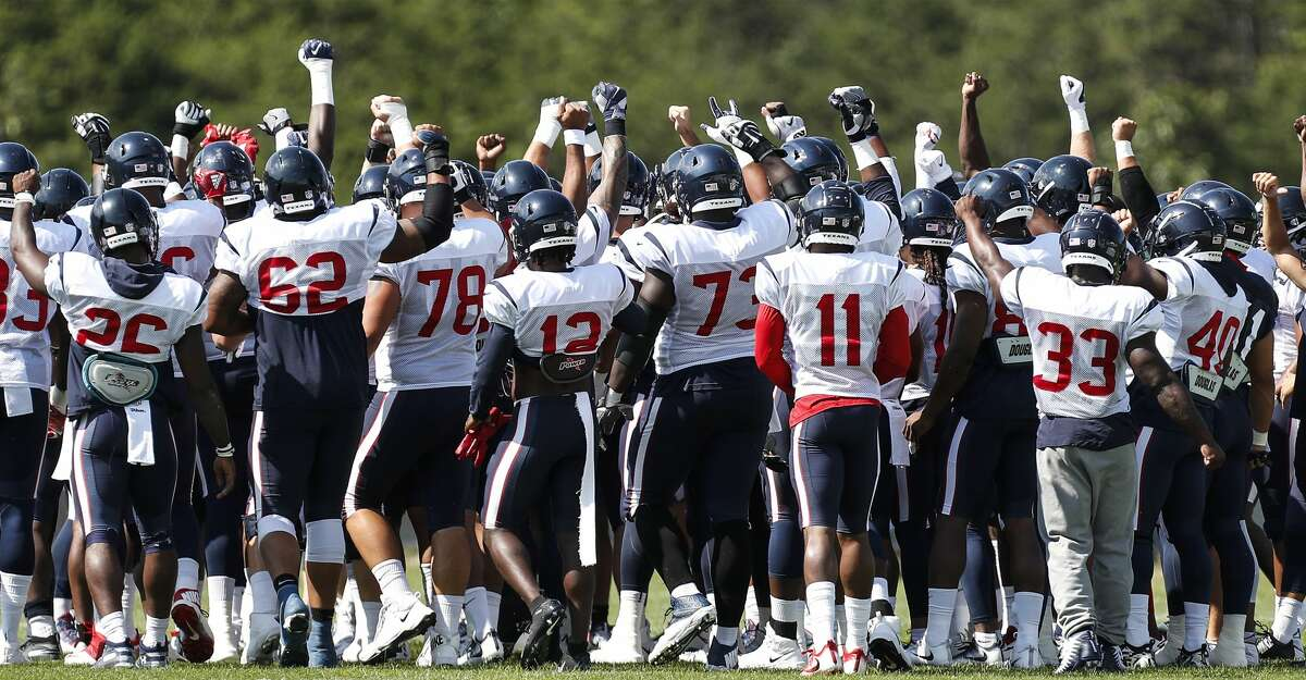 Houston Texans players raise their fists as they break their team huddle at the beginning of practice during training camp at the Greenbrier Sports Performance Center on Sunday, July 29, 2018, in White Sulphur Springs, W.Va.