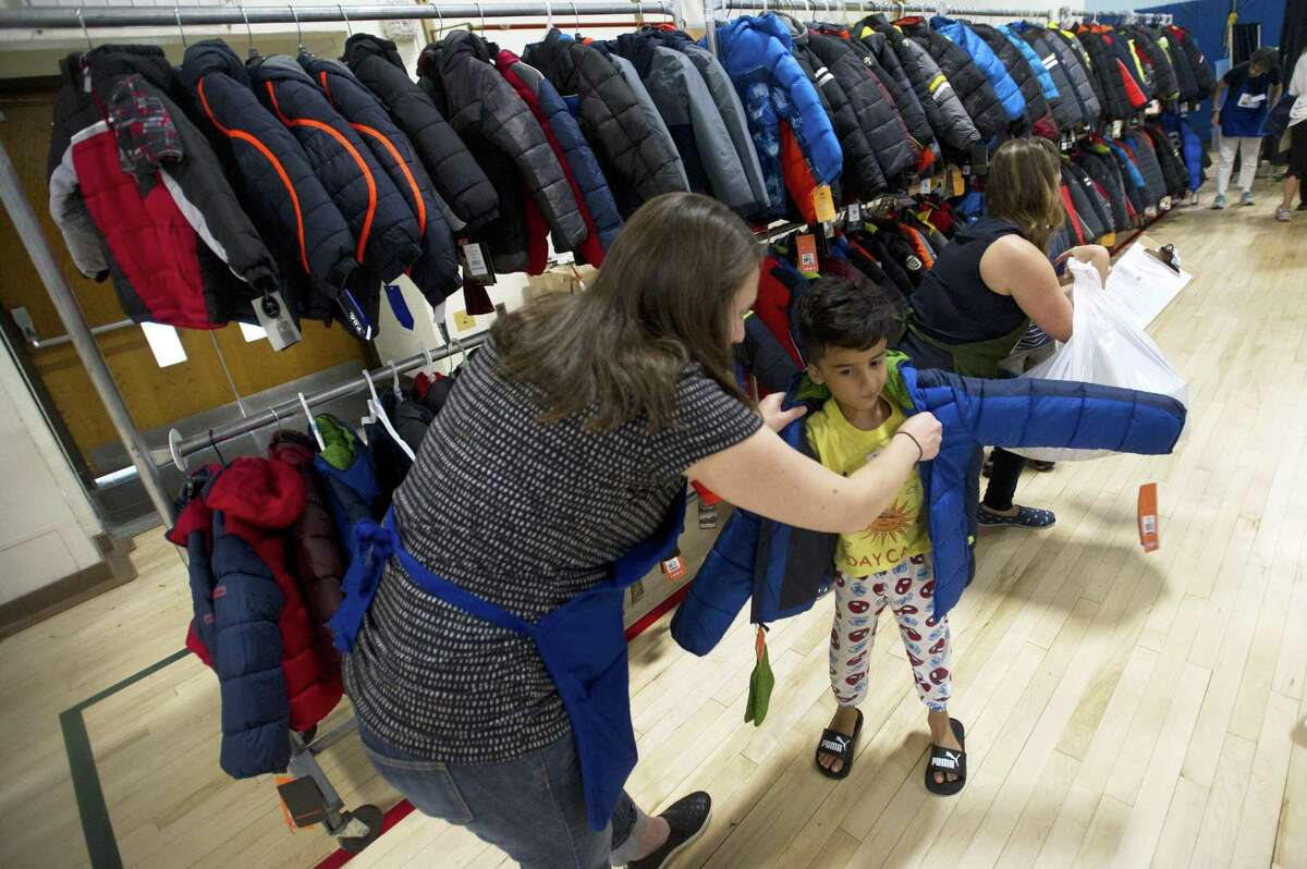 Kyle Robles-Castro, a student at KT Murphy School, tries on a winter jacket during the annual Back to School Shop inside Davenport Elementary School in Stamford, Conn. on Sunday, July 29, 2018. The giveaway included a backpack with school supplies, new shoes, a new winter coat and other clothes items like shoes and socks.