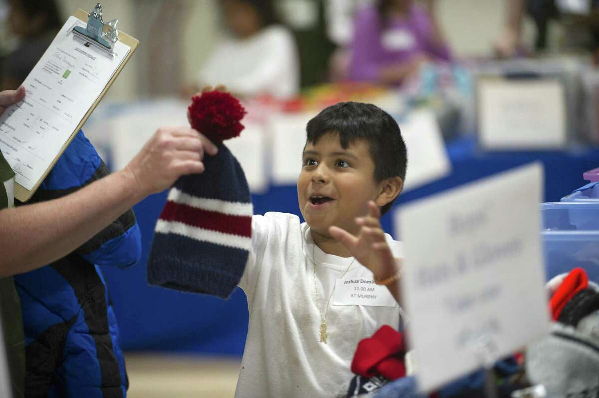 Joshua Dominguez, a student at KT Murphy School, reacts to the winter hat he likes during the annual Back to School Shop inside Davenport Elementary School in Stamford, Conn. on Sunday, July 29, 2018. The giveaway included a backpack with school supplies, new shoes, a new winter coat and other clothes items like shoes and socks.