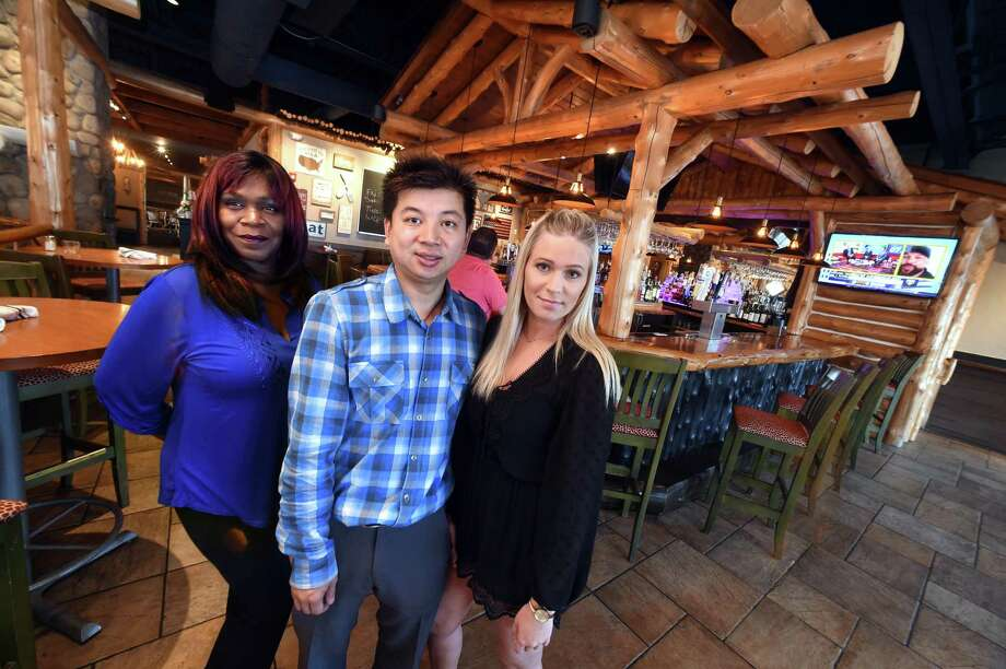 From left, manager Valentina Coatanroch and owners Eddy Zheng and Sarah Belke pause in the newly opened Fireside Bar and Grill in Orange Friday. Photo: Arnold Gold / Hearst Connecticut Media / New Haven Register
