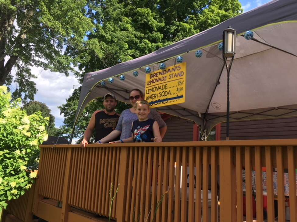 From left, Sean, Jodi and Brendan Mulvaney stand on the deck of their home where 7-year-old Brendan's lemonade stand was shut down by a woman who appeared to be with the state Department of Health on Friday, July 27, in Ballston Spa.